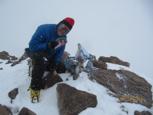 Dave on the summit of Aconcagua, holding photos of his sons