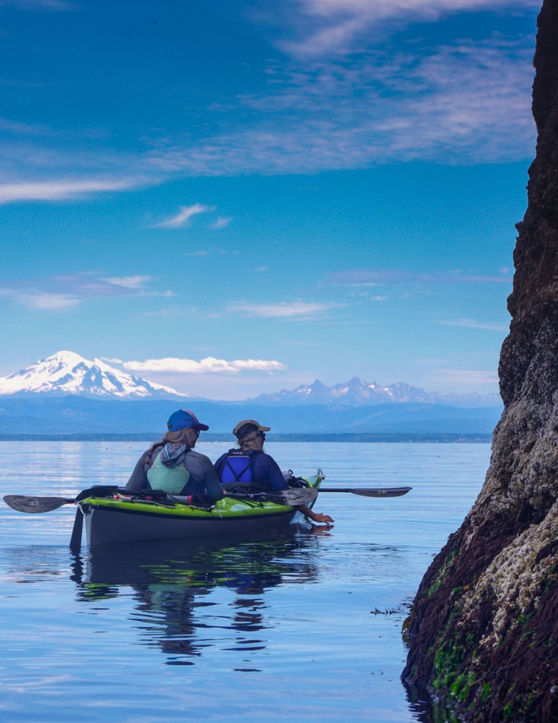 Exploring inter-tidal life on the edge of Sucia Island with Mt. Baker in the background. Photo by Kristi Kucera/ Moondance Sea Kayak Adventures
