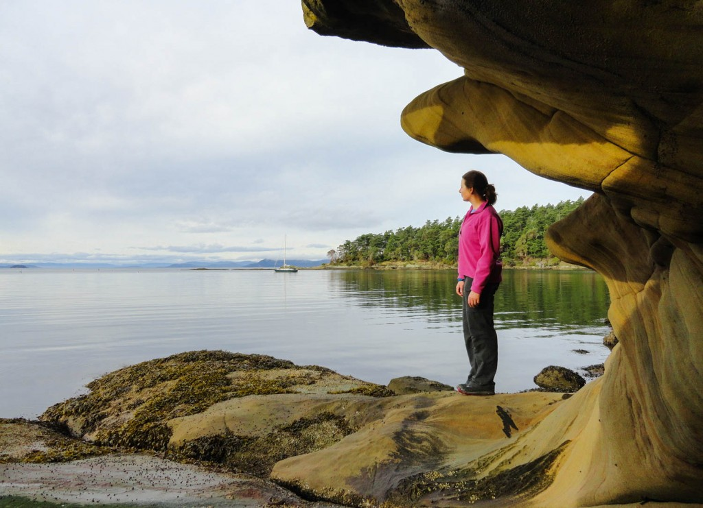 A hiker pauses under sandstone ledges along Sucia Island's Shallow Bay. Photo by Craig Romano